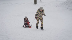 Young mother rolls her daughter on sledding in the park. Winter active family Stock Footage