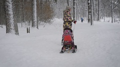 Young happy mother unning ahead on the path in winter forest and pulling along Stock Footage