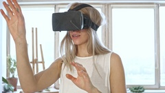 Slow motion of blonde woman in white space trying virtual reality glasses. Stock Footage
