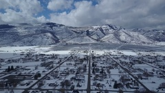 Aerial flight rural city homes winter snow mountain valley 2 4K Stock Footage