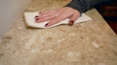 Young woman wiping the dust from the marble surface with white cloth. Cleaning Stock Footage
