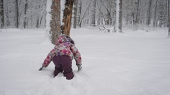 Little girl playing with snow, clearing himself a path in snow-covered park in Stock Footage