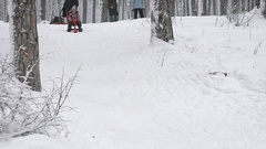 Close up of happy little girl in skiing outfit, sitting on her red sleigh and Stock Footage
