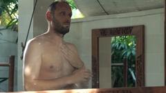 Man applying moisturizing cream on his arm in bathroom  Stock Footage