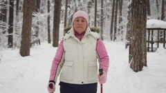 An elderly woman in a beautiful sports wear is engaged in Nordic walking on a Stock Footage