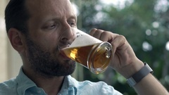 Happy, young man drinking beer in garden in cafe Stock Footage
