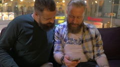 Close up view of two white mature bearded men using smartphone together Stock Footage