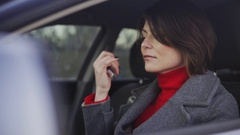 Business woman in grey coat and red turtleneck applying makeup in the car Stock Footage