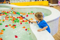 Cute boy in the playroom fishing. The development of fine motor concept. Cr.. Stock Photos