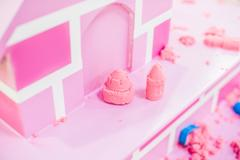 Figures from the pink kinetic sand The development of fine motor concept. C.. Stock Photos