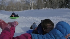 Three happy kids sledding slow motion Stock Footage