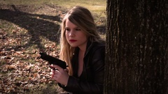 Female Secret Agent hides behind tree with gun   Action Movie Shots Stock Footage