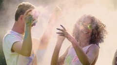 Two couples in love spraying colorful paint at each other during Holi festival Stock Footage