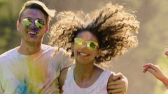 Couples in love having good time, enjoying the Festival of colors in slow motion Stock Footage