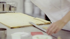Woman puts one small piece of dough on a big piece to cut the equal pieces Stock Footage