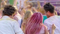 Crowd of young people covered in colored paint dancing at open air music fest Stock Footage