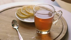 Rotating wooden background with tea and slices of lemon Stock Footage