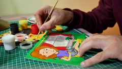 Man in the process of drawing with acrylic paints picture with red-haired girl Stock Footage