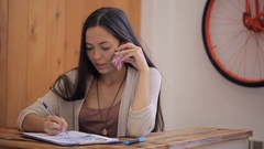 Female talking on telephone, writing in documents inside office Stock Footage