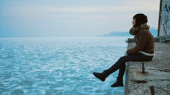 Young girl sits on a stone pier near the frozen ice sea Stock Footage