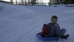 Boy at bottom of sledding hill Stock Footage