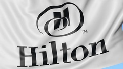 Close-up of waving flag with Hilton Hotels Resorts logo, seamless loop, blue Arkistovideo