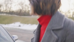 Attractive business woman in grey coat opening the car's bonnet and looking Stock Footage