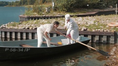 Man in white and nurse in boat on lake use paddling oar on summer sunny day Stock Footage