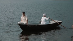 Nurse paddling boat on lake, man in white clothes grimacing and joking Stock Footage