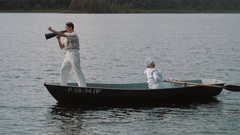 Nurse paddling boat on lake, man in white clothes commands into speaker Stock Footage