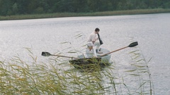 Nurse rowing boat on lake, man in white clothes commands into megaphone Stock Footage