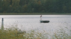 Nurse rowing boat on lake, man in white clothes commands into speaker Stock Footage