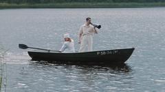 Nurse paddling boat on lake, man in hair net yelling into megaphone Stock Footage