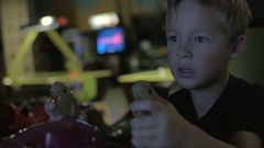 Close up view of small boy are playing video arcade game in game center Stock Footage