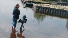 Cameraman standing knee deep in water with camera on tripod on summer sunny day Stock Footage