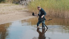 Cameraman standing knee deep in water with camera on tripod near reeds sunny day Stock Footage