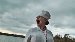 Nurse turn her head and start screaming at lake on summer cloudy day Stock Footage