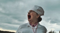 Nurse turn her head and start yelling at lake on summer cloudy day Stock Footage