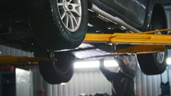 Car lifted in automobile service for repairing, worker fixing faults Stock Footage
