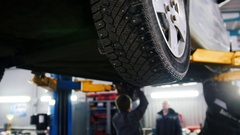 Car lifted in automobile service for repairing, workers fixing faults, slider Stock Footage