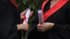 Female graduates in academic dresses holding diplomas and talking about future Stock Footage