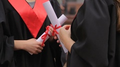 Hands of female graduates holding diplomas tied with red ribbons, conversation Stock Footage