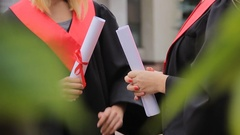 Female graduating students holding diplomas tied with red ribbons and chatting Stock Footage