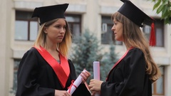 Attractive female graduates holding diplomas and talking about future career Stock Footage