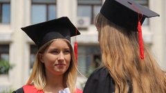 Blond woman in academic cap listening to best friend at graduation ceremony Stock Footage