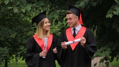 Smiling couple of graduates walking in park, holding diplomas and talking Stock Footage