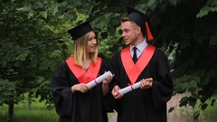 Woman and man in academic dresses holding diplomas, talking and walking in park Stock Footage