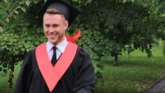 Pleased man in academic dress holding diploma, walking and jumping in park Stock Footage