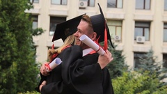Best friends in academic dresses and hats hugging and smiling on graduation day Stock Footage