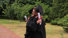 Happy graduates holding diplomas and embracing in park near academy, joy Stock Footage